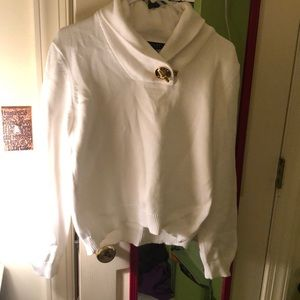White sweater polo with gold buckle on neck.